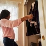 woman picking out an outfit from the clothes in her closet