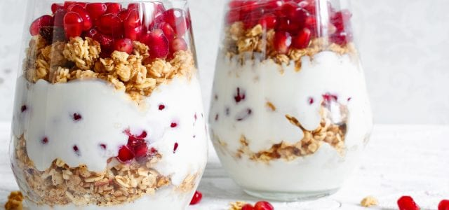 homemade yogurt parfait with granola and pomegranate fruit in glasses on white wooden table. delicious dessert. healthy breakfast