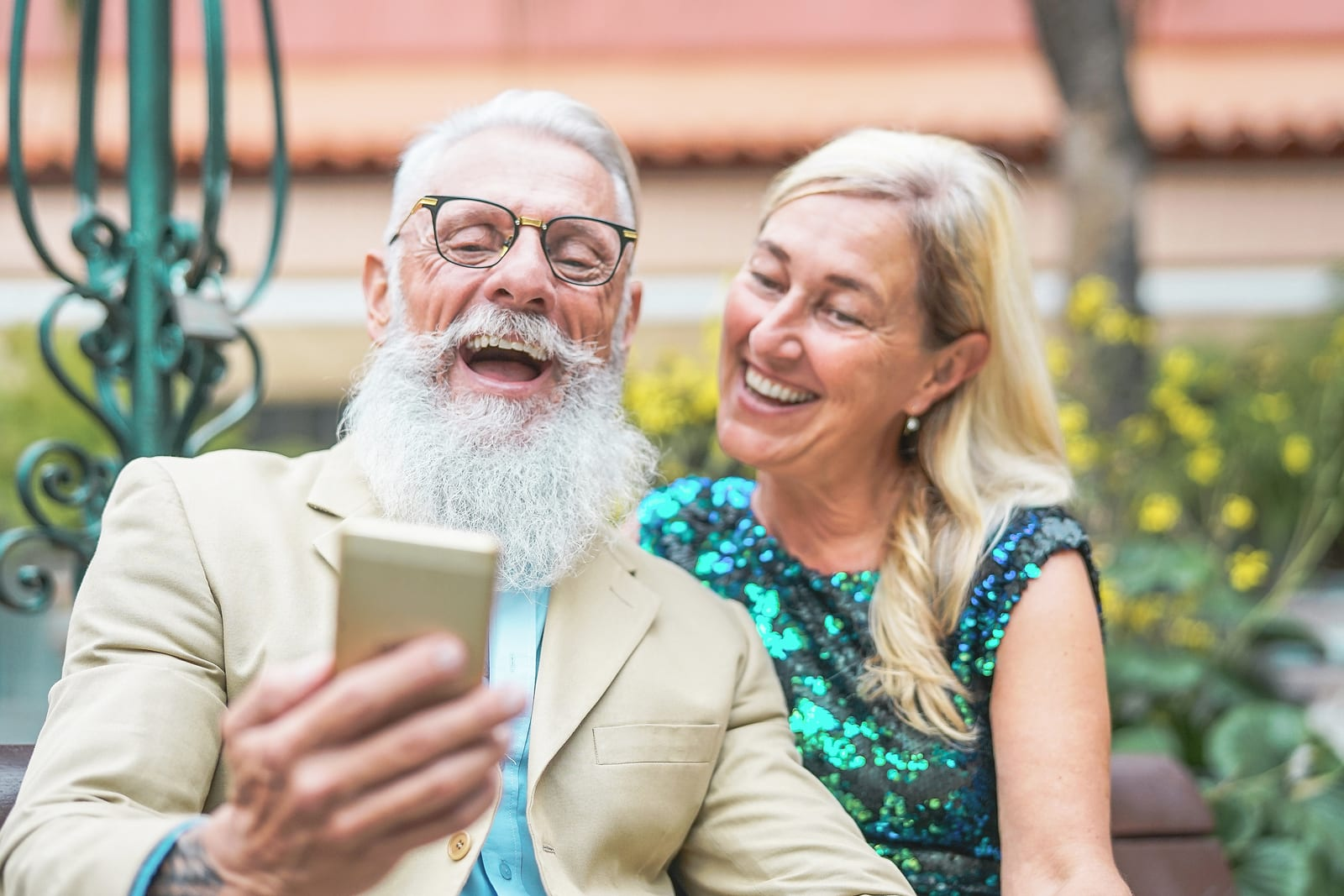 Happy senior couple watching on mobile smart phone and laughing together - Mature fashion people having fun with new technology cellphones outdoor - Social, pensioners, tech, elderly lifestyle concept