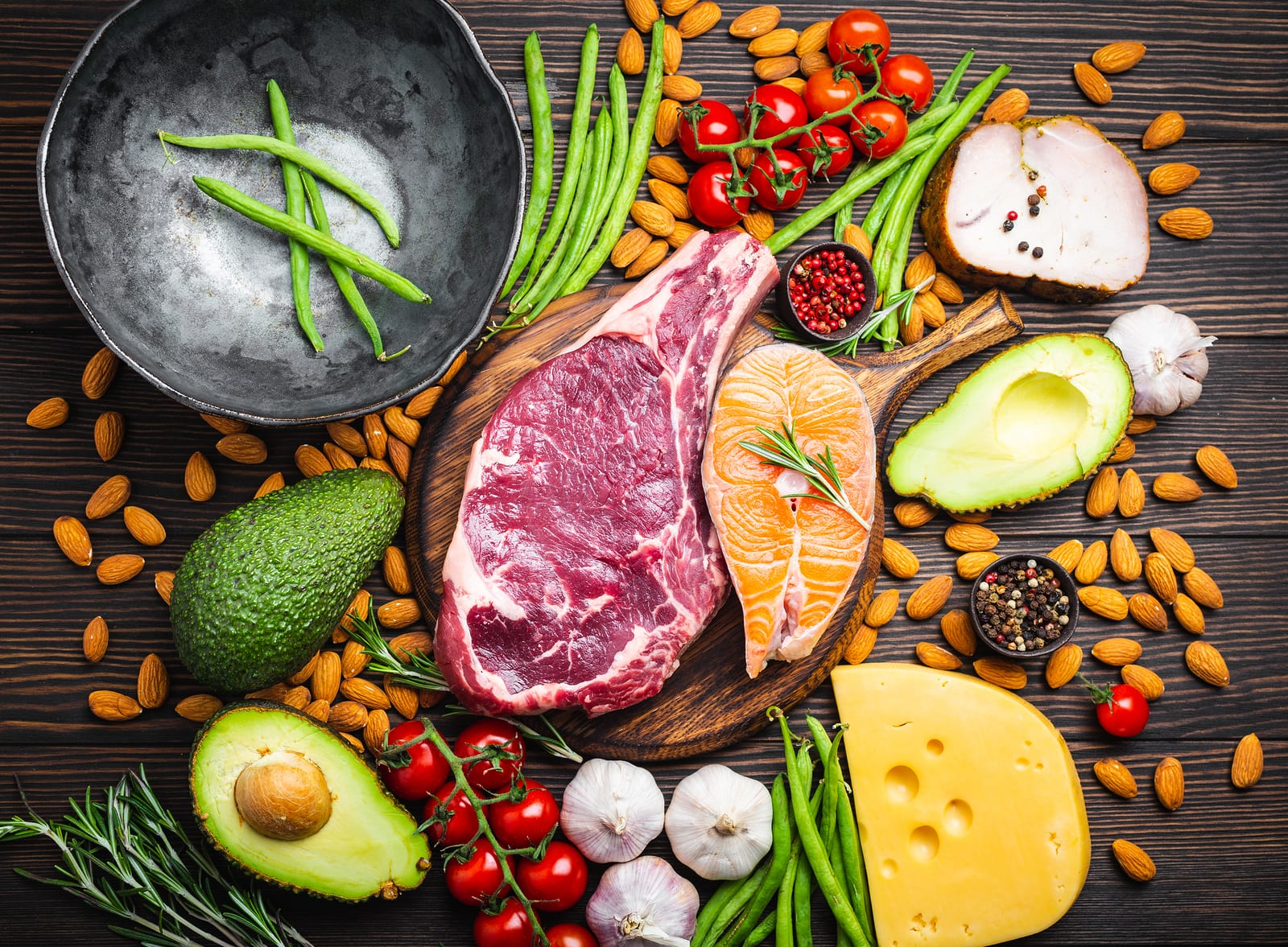 A healthy balanced diet of red meat, fatty fish, and other healthy options are laid out in an appetizing arrangement on a wooden table.