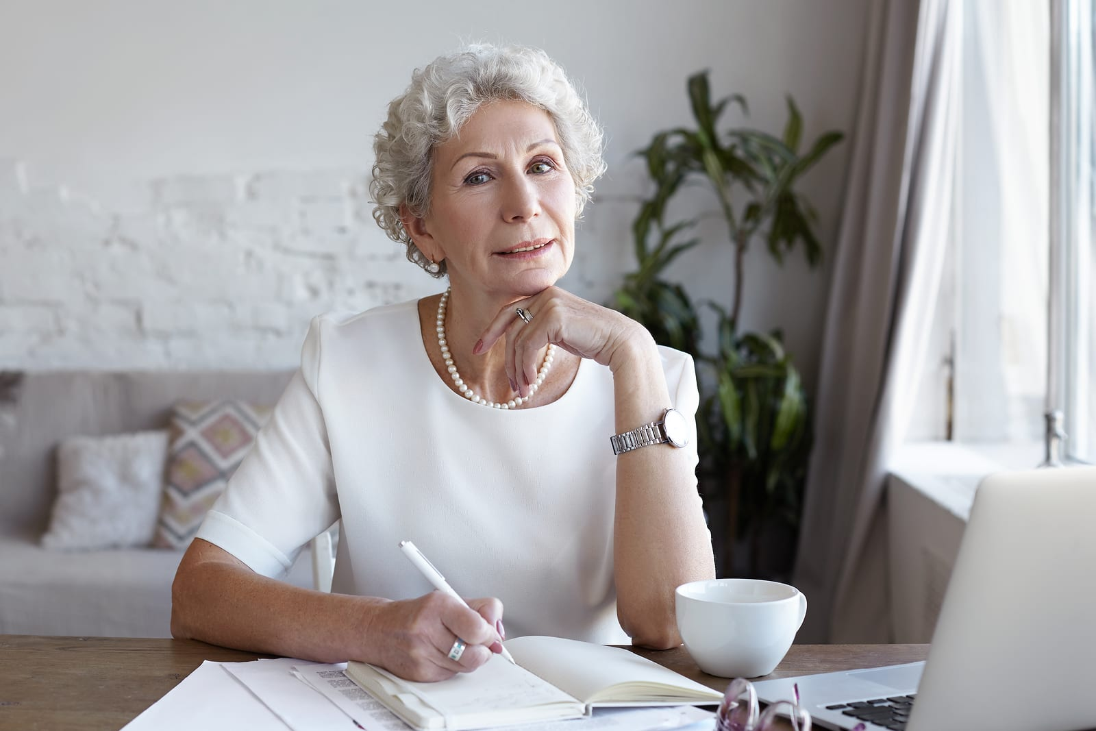 Senior people, modern lifestyle, technologies, job and occupation concept. Mature woman writer with short gray hair using wifi on laptop computer and making notes in copybook, working on new article