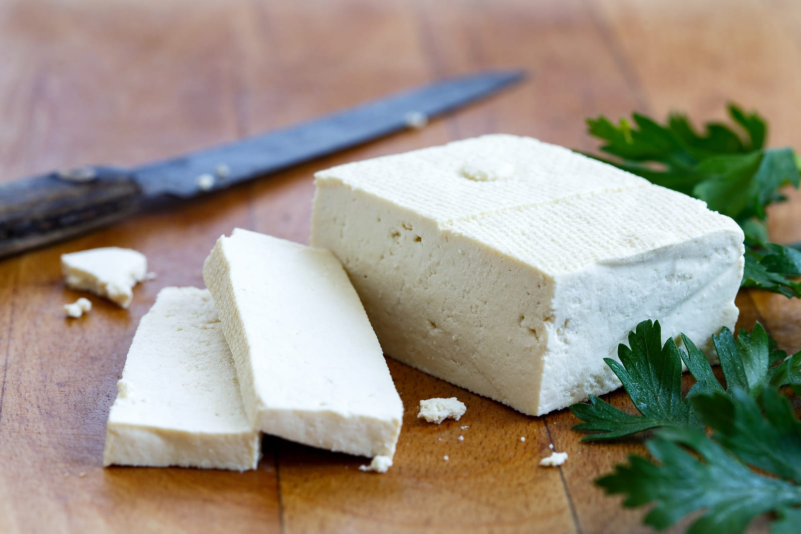 Single block of white tofu with two tofu slices crumbs fresh parsley and rustic knife on wooden chopping board.