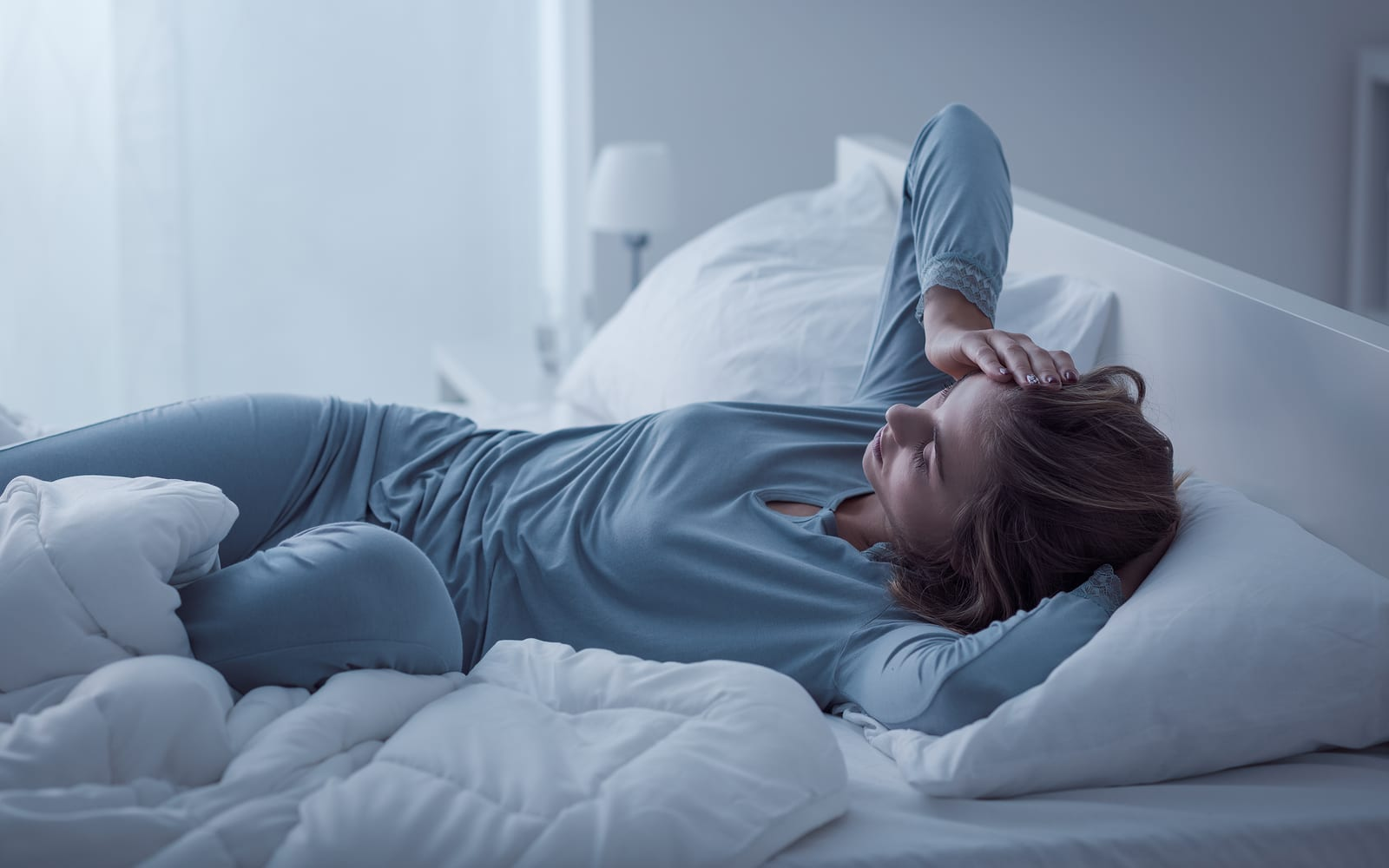 Depressed woman awake in the night she is exhausted and suffering from insomnia