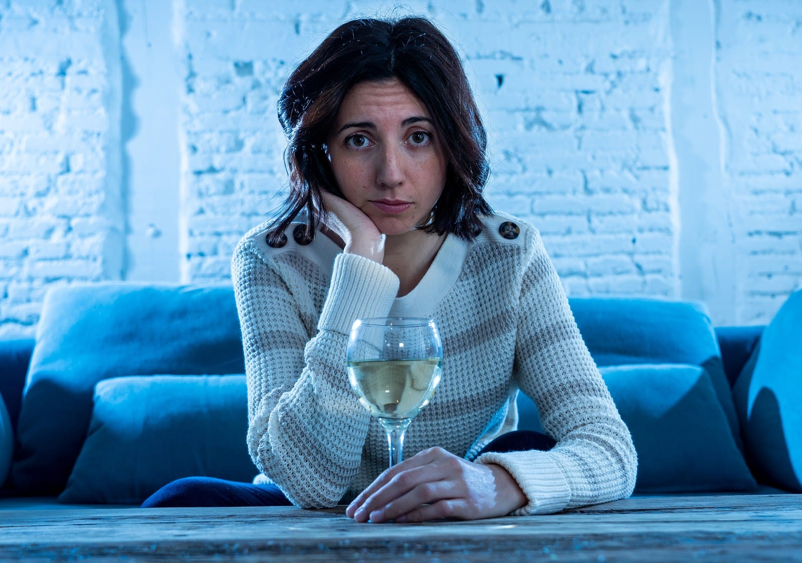 Woman drinking wine on a couch