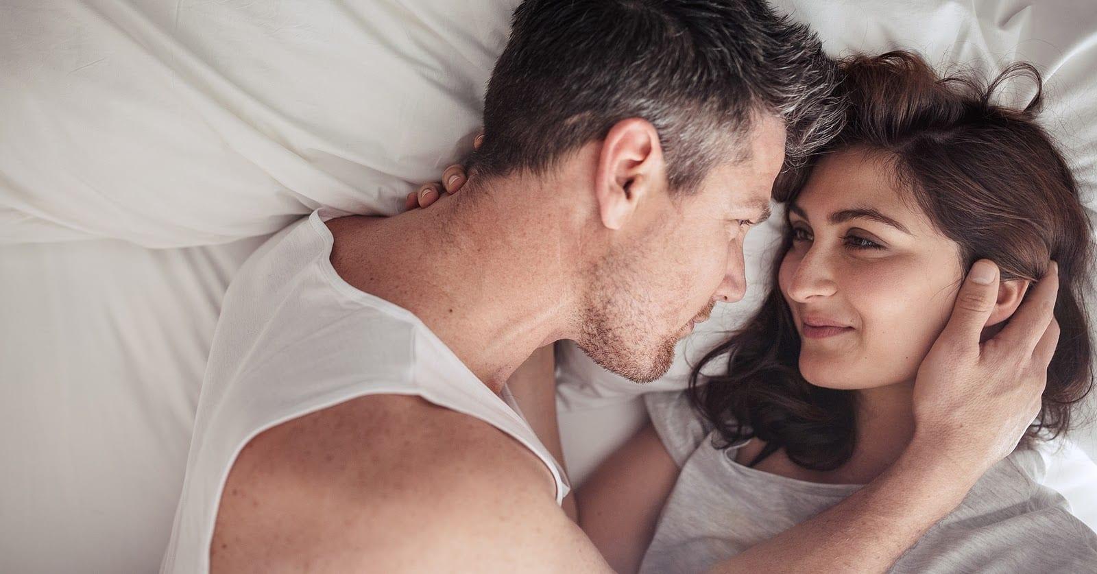 heterosexual couple in laying in bed