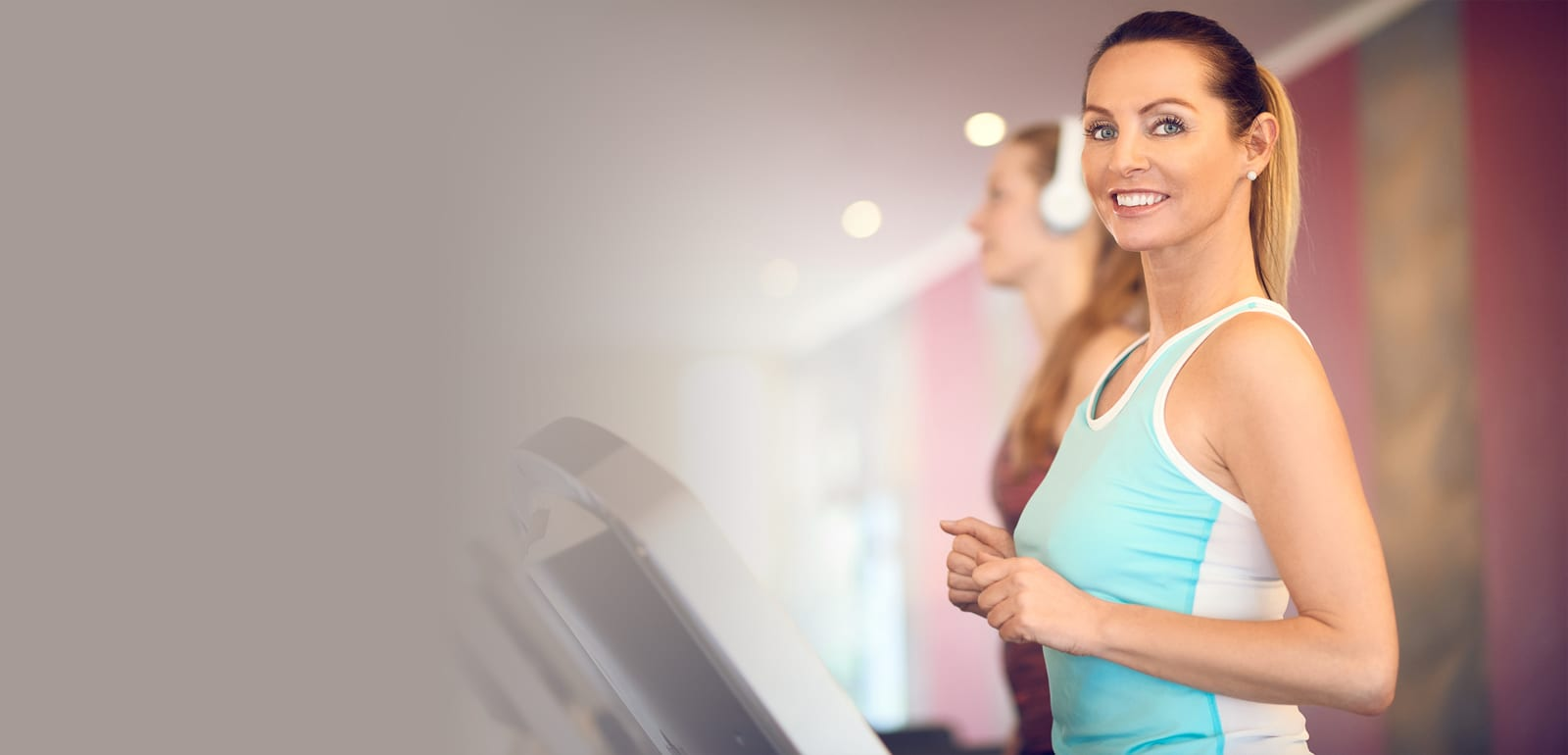 woman working out on a treadmill smiling at the camera